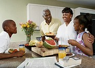 Family Stood Around a Kitchen Counter Having Fruit for Breakfast