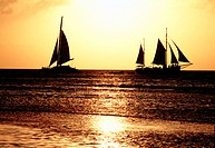Sailboats at sunset crossing wakes in Aruba. Dutch Antilles