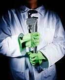 Female in a white laboratory coat wearing green rubber gloves holding a monkey wrench