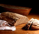 A loaf of rye bread, slice cut, on wooden background