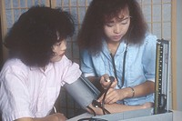 Photograph of a young woman having her blood pressure checked by a nurse. Both women are of Southeast Asian Hmong ethnicity.