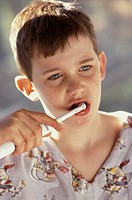 Nine-year-old boy with braces brushing his teeth with an electric toothbrush.