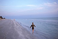 Boy running on a beach at dusk.
