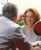 Young woman trying on a pair of glasses at the optometrist´s office. A male optometrist is helping her.