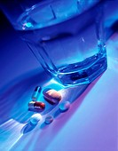 A glass of water with it´s shadow cast over a variety of pills and capsules lying next to it.