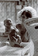 Female nurse weighing a newborn baby boy shortly after birth.