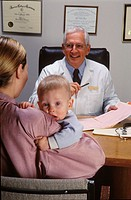 Male doctor seated behind his desk in consultation with a mother holding her baby.