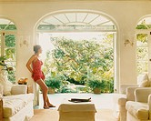 Woman Leaning in a Living Room Looking Out Onto a Lush Garden