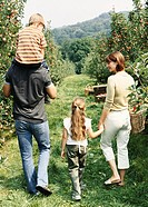 Family Walking in an Orchard, With the Mother Holding a Basket of Fruit and the Father Carrying His Son on His Shoulders