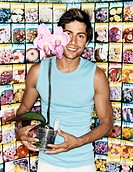 Portrait of a Young Man Holding a Potted Orchid in a Gardening Shop