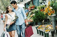 A Young Couple Walk Side by Side By a Florist´s Shop Looking at Each Other, Carrying Shopping Bags and a Bouquet of Flowers