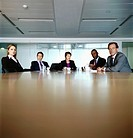 Five Business People Sat at the far end of a Table in a Conference Room