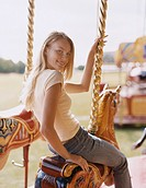 Young Woman Sitting on a Carousel Horse, Flirtatiously Looking back at the Camera