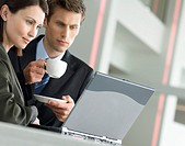 Businessman Holding a Cup and Saucer With a Businesswoman, Both Looking Down at a Laptop Computer