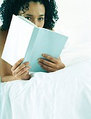 Woman lying on stomach on bed, reading book