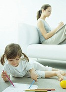 Little girl lying on floor coloring, young woman sitting behind her on couch writing with knees up (thumbnail)