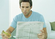 Young man reading newspaper and eating sandwich