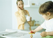 Little girl playing with toy, woman holding mug and talking on phone in background