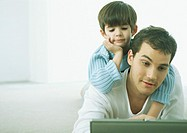 Little boy on man's back, both looking down at laptop