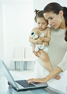 Woman holding little girl in one arm, typing on laptop with other hand
