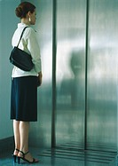 Woman waiting for elevator, full length
