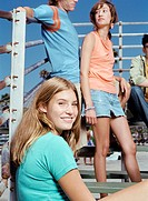 Teenage Girl With Friends Sitting on Benches by Railings