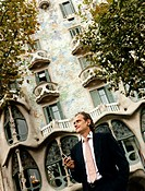 Businessman Stands in Front of Casa Batllo Using His Mobile Phone, Barcelona, Spain