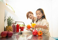 Mother and Daughter Washing Peppers at a Kitchen Sink