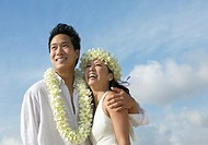 Newlywed Couple Wearing Flower Garlands Stand Against a Summer Sky
