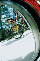 View of cyclists through wheel