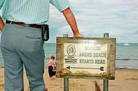Man leaning on sign at beach