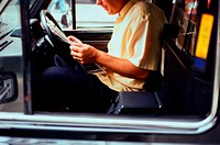 Taxi driver reading a newspaper