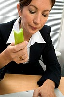 Businesswoman eating celery
