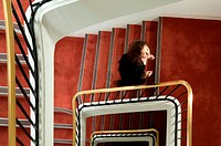 Businesswoman walking up spiral stairway