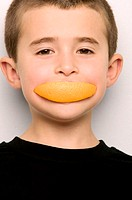 Boy with orange segment in mouth