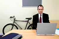 Businessman with mountain bike in office