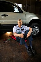 Portrait of a mechanic sitting on a creeper near a car