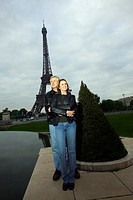 A smiling couple standing in Paris