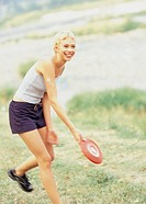 woman playing frisbee, outdoors