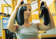 woman on a pectoral machine in gym
