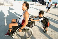 Boy pushes father´s wheelchair. Domestic Violence March event, Safespace Foundation. Ocean Drive. Atlantic Shore. South Beach. Miami Beach. Florida. U...