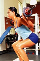 Young fit woman in gym working out squatting weights.