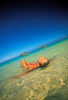 Hawaii, Oahu, woman floating in ocean at Lanikai beach, Mokulua Islands in background