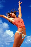 Teen girl with arms spread up against clear blue sky, joy/freedom.
