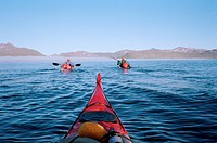 Part of a kayak and two people rowing kayaks in front, mountains ahead