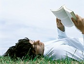 Young man lying on back in grass reading book, head and shoulders