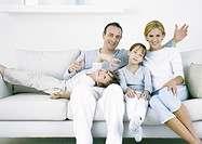Parents with sitting on sofa with daughter and son, looking at camera