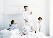 Girl and boys having pillow fight with man