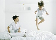 Boys on bed, one in mid air