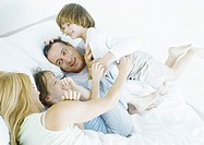 Parents with daughter and son in bed, smiling